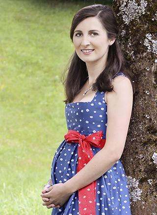 Frau im blau-weißen Umstandsdirndl mit roter Schleife