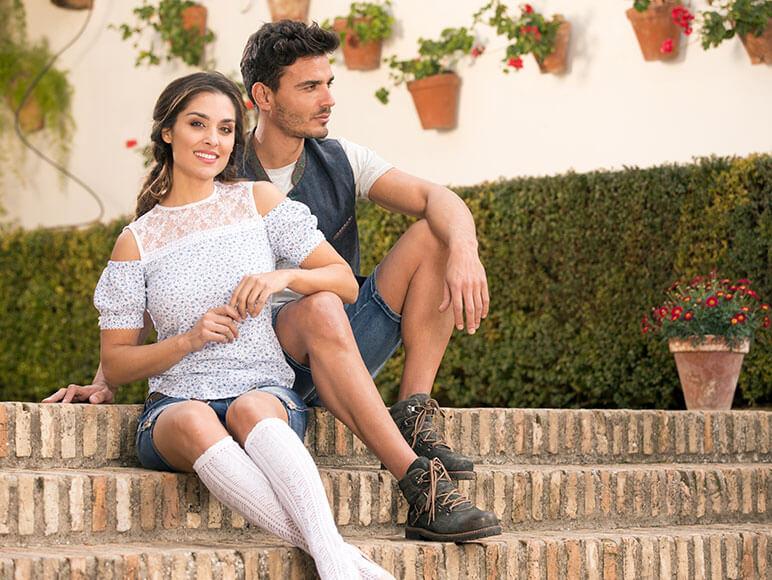 Mann in Tracht mit braunen Trachtenschuhen als Boots und Frau in Tracht mit weißen Trachtenstrümpfen sitzen auf Treppe